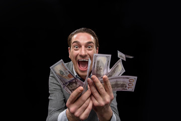 Passion about cash. Portrait of young insane man in suit is standing and showing a lot of money while looking at camera with desire and open mouth. Isolated on dark background