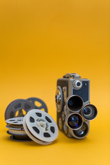 Vintage cinema camera and reels over yellow background