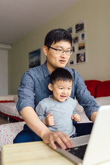 Adorable boy and his father using laptop at home