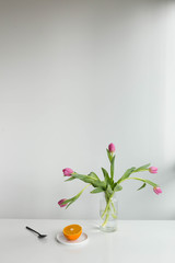 Morning with sliced orange and pink tulips in vase