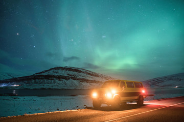 Camper van at night in Iceland surrounded by snowy mountains under northern lights