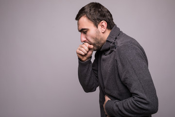 Handsome man with beard coughing a lot on grey background