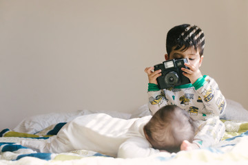 Toddler taking picture of baby sister with toy camera