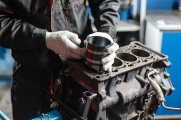 the mechanic installs a new piston. Disassemble engine block vehicle. Motor capital repair. Sixteen valves and four cylinder. Car service concept.