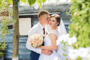 Young wedding couple enjoying romantic moments outside on a summer day