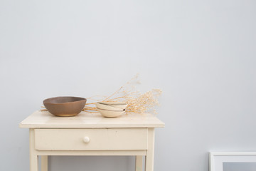 Wooden table with ceramics and dry flowers in front of a grey wall