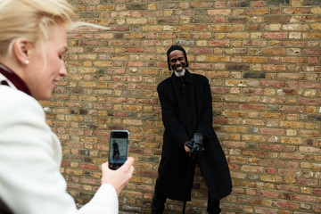 Smiling man with cane posing against brick wall to woman with mo