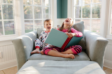 Big sister reading a book for little brother