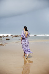 A beautiful woman walking along the beach on a dark day