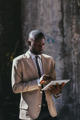 Black businessman holding a tablet in the street