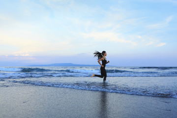 Asian woman running  at a beach