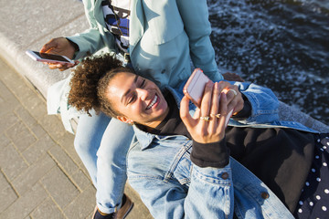Young black woman laying on her friend's lap, using her phone.
