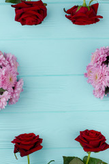 Frame with flowers, wooden background. Fresh roses and chrysanthemums on blue wooden background with space for text in the center. Valentines Day greeting card.