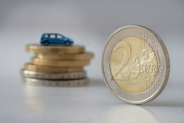A coin rolls to a stack of coins on which a family sedan stands.