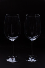 Two empty wine glass on black background. Fragile blank glasses for wine on dark background. Romance and celebration.
