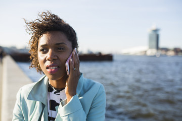Portrait of a young black woman, calling with her phone.