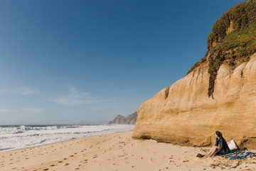 Girl sits on a blanket on the beach on a sunny day, against the cliff