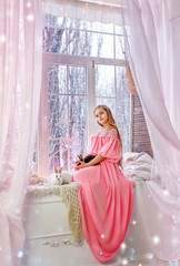 nice girl in pink dress sits on window sill by the window, holding rabbit