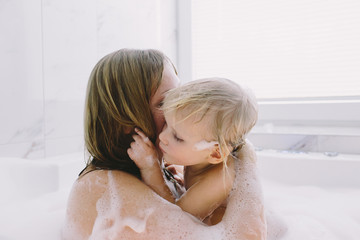Mother and daughter embracing in bubble bath