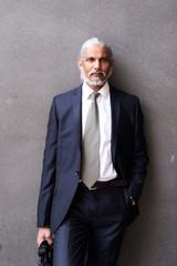 Elegant businessman against grey background.