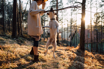 Woman playing with her dog in the forest