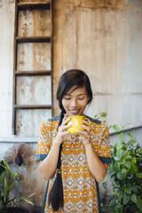 Asian Woman Having Tea/Coffee on Balcony