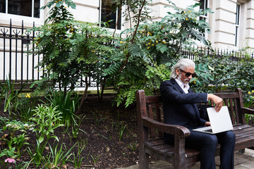Gray-haired businessman in sunglasses working on laptop on bench.