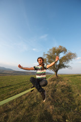 Young man sitting on slackline in lotus position