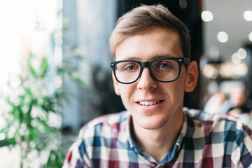 Portrait of a young man in glasses and a shirt with a positive mood and a wide smile