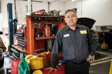 Asian car mechanic standing in his auto repair shop