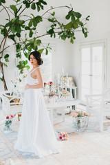 Brunette Bride Looking Over Shoulder in White Room