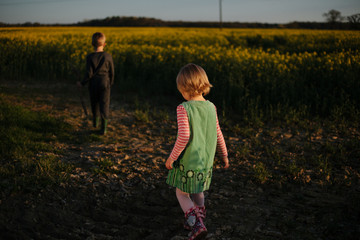 Siblings walk in fields at sunset.