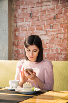Woman browsing phone in cafe
