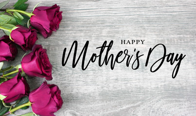 Wall Mural - Happy Mother's Day Calligraphy with Pink Roses Over Rustic Wood Background