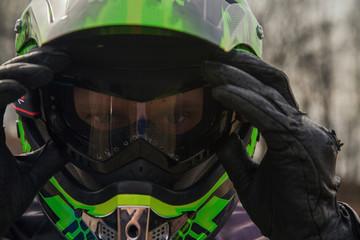 A biker adjusting goggles