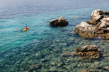 Young man exploring rocky Mediterranean coastline by kayak