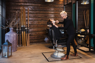 Female Barber Shaving Client's Face In Shop