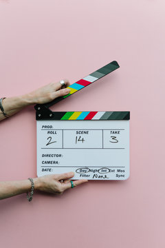 Woman holding clapperboard over pink background