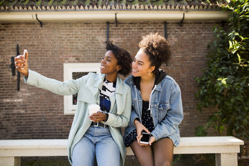 Two young women, having fun with their phone.