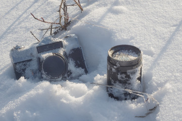 retro camera and lens in the snow in the woods