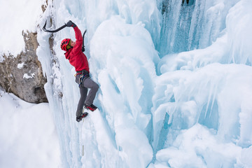 Young woman wearing red jacket ice climbing on frozen waterfall