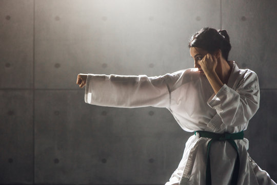 Martial arts Concept. Young woman in kimono practicing karate