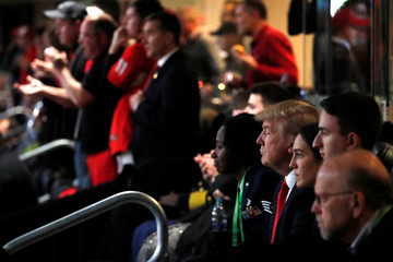 U.S. President Donald Trump, flanked by ROTC students, attends the NCAA College Football Playoff Championship game between Alabama and Georgia in Atlanta