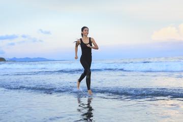 Asian woman running  at a beach