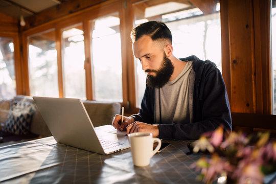 Bearded man working on a laptop