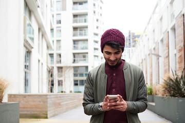 Smiling man in purple hat browsing mobile phone.