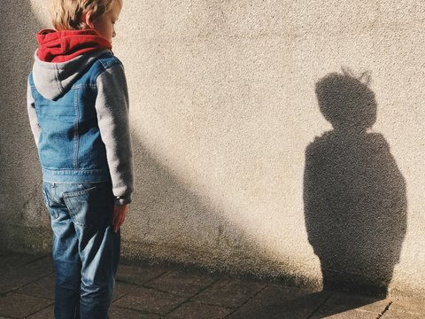 Child stood looking at his shadow on the wall