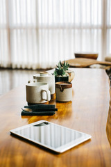 Rustic Wooden Table With Ceramic Teaware and Digital Tablet in Bright Living Room