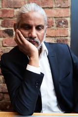 Sad businessman leaning against hand.