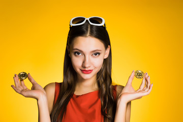 confident attractive girl holding golden bitcoins, thinking about crypto currency